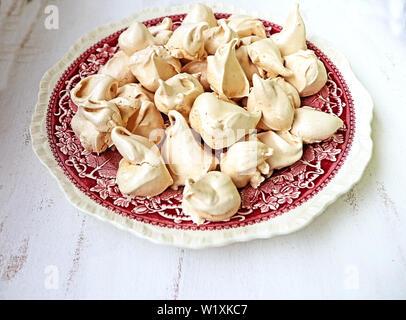 Des meringues à la vanille et cannelle sur une plaque de céramique vintage, délicieux dessert