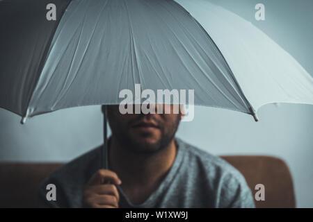Jeune homme au parapluie blanc assis sur un canapé à la maison - concept de sécurité - ne pas prendre des risques concept