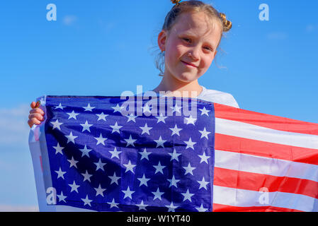 Close-up portrait d'un jeune adolescent smiling girl holding le drapeau américain sur fond de ciel bleu. Banque D'Images