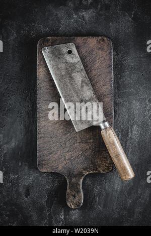 Planche à découper et le rustique couperet à viande sur fond sombre. Boucherie de l'outil. Banque D'Images