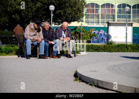 Trois personnes âgées, homme assis sur un banc de parc d'avoir une discussion à Rijeka, Croatie. Avril 2019 Banque D'Images