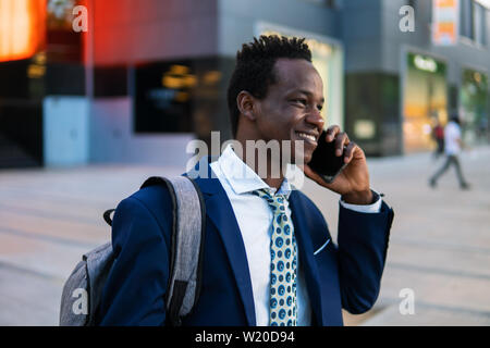 African American businessman holding mobile phone portant costume bleu