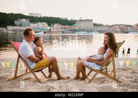 Dans une station familiale en plein air soirée cafe. Mère et père et ses deux fils s'asseoir sur des chaises longues, à la recherche au coucher du soleil sur plage de sable près de river Banque D'Images