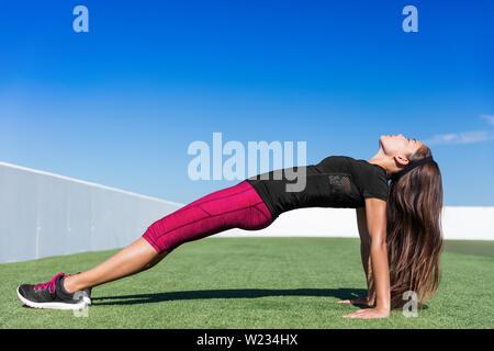Remise en forme de yoga étirement vers le haut du corps femme planche faisant de l'exercice en plein air sur les planches de marche arrière de l'herbe du parc. Femme Sport la formation de force son corps ayant un poids corporel de base des exercices de flexibilité. Banque D'Images