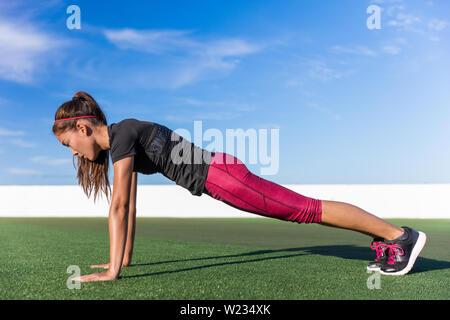 Femme Fitness faire l'exercice de poids des planches pour la force de noyau de la formation. Active girl pratiquer la planche de yoga pour les abdominaux en été en plein air vivant une vie digne. Banque D'Images
