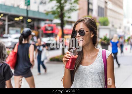 Le mode de vie urbain hipster asian woman drinking fruits sains légumes Jus de fruits smoothie marche sur rue du centre-ville de New York City, New York, USA. Jeunes adultes en bonne santé diète concept.