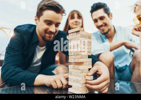 La compagnie des jeunes gens jouer shaan. Jeunes amis au coucher du soleil sur la terrasse penthouse jenga jeu