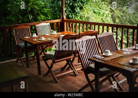 Chaises et tables en bois vide, avec les tasses de café à l'envers - prêt pour le petit déjeuner du matin, jungle rainforest en arrière-plan Banque D'Images