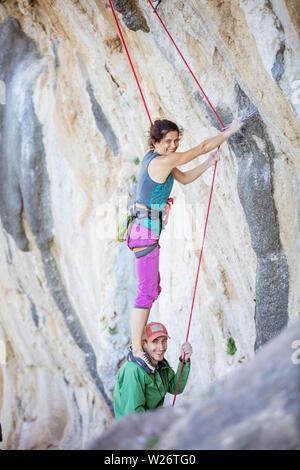 Cheerful female rock climber debout sur les épaules de son partenaire afin de commencer l'escalade itinéraire difficile Banque D'Images