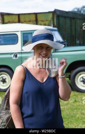 90e Kent County Show, Detling, le 6 juillet 2019. Femme dans un chapeau de paille vêtu d'un haut bleu se trouve en face d'un Landrover. Banque D'Images