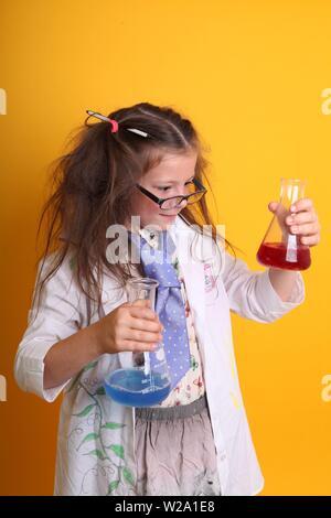 MR - Science Geek Jeune fille / femme dans les verres de 7 ans Enfant de la bouillie (produits chimiques dans des béchers en verre borosilicaté science portrait sur fond jaune Banque D'Images