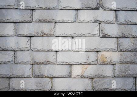 Partie d'un toit de tuiles d'ardoise altérée olf comme arrière-plan.Closeup détail modèle de carreaux en pierre grise Banque D'Images