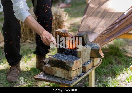 La main avec un morceau de fer chauffé dans un feu de charbon et les soufflets faire les étincelles d'outils de forgeron. Le processus de création d'outils de métal et d'armes Banque D'Images