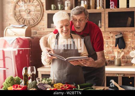 Senior couple preparing déjeuner avec livre de recettes Banque D'Images