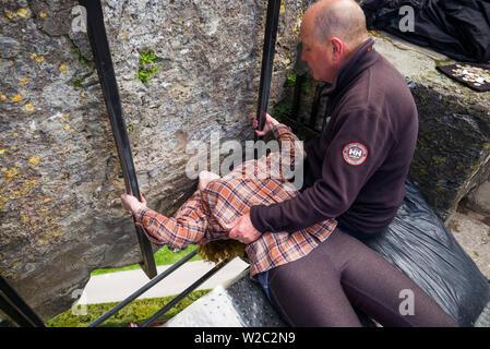 L'Irlande, dans le comté de Cork, le château de Blarney, Blarney, 15e siècle, les visiteurs s'embrasser la pierre de Blarney Banque D'Images