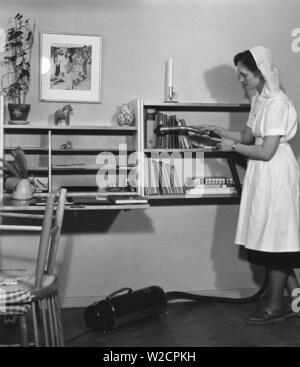 L'aspirateur dans les années 1950. Le jeune étudiant Gertrud Larsson est d'avoir une journée de nettoyage dans son appartement d'étudiants. Elle est minutieuse et même les livres de l'étagère obtient une bonne aspiration. Suède 1954 Banque D'Images