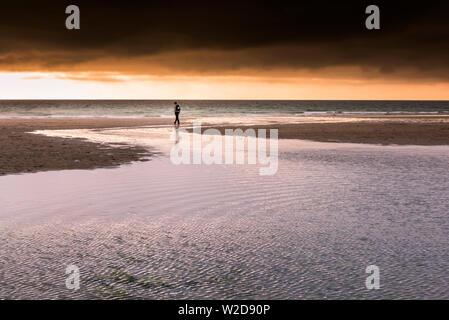 Un adolescent de marcher seul au coucher du soleil sur la plage de Fistral à Newquay en Cornouailles.