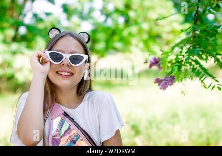 Sourire et happy teen girl in drôle de lunettes blanches avec un casque sans fil et de longs cheveux blonds sur un jour d'été ensoleillé à proximité d'une floraison vert bu Banque D'Images