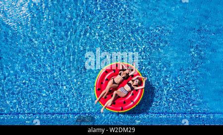 Le temps de vous détendre. Vue du dessus de l'attractive young woman in bikini smiling tout en vous relaxant dans la piscine avec petite amie Banque D'Images