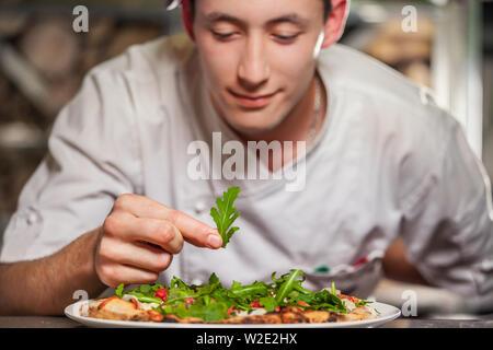 Young male cook la préparation de délicieux amuse-bouche avec des herbes on white plate Banque D'Images