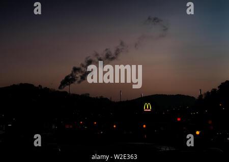 Une épaisse fumée noire sur les toits de la ville de Duck avec un McDonalds signer brillants dans l'arrière-plan. Banque D'Images