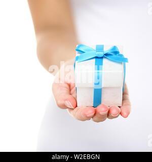 Boîte-cadeau / présent ou cadeau de noël part close up. Boîte cadeau décoratif attachées avec un ruban turquoise et bow bombée soigneusement composée de femmes comme elle donne un cadeau surprise à un être cher. Isolées. Banque D'Images