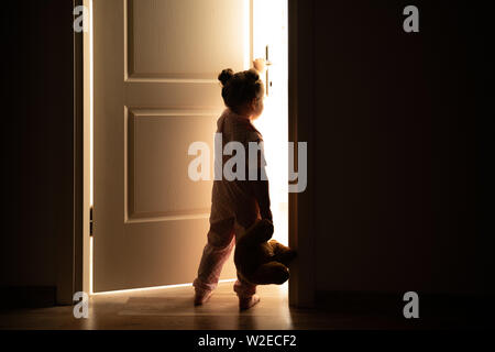Petite fille ouvre la porte à la lumière dans l'obscurité. Banque D'Images