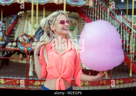 Jeune blond woman holding pink Cotton Candy et rire. Banque D'Images