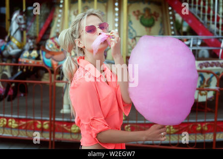 Young blonde woman eating Cotton Candy rose. Banque D'Images