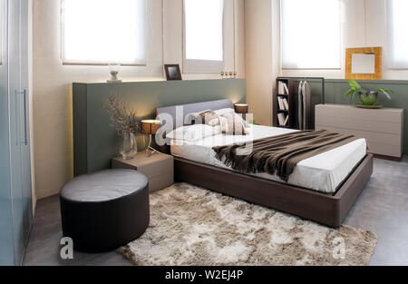 Luxe moderne chambre monochrome marron intérieur avec grand au-dessus d'une tête de lits doubles avec des armoires, et ottomane construite en armoire Banque D'Images