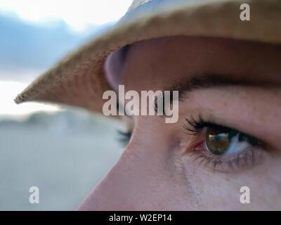 Portrait d'une brune aux yeux bruns dans un chapeau a l'air sur le côté