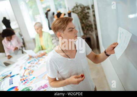 Travailler sur un croquis. Jeune homme blond motivés à la recherche à son croquis tout en maintenant un aimant rouge dans sa main Banque D'Images