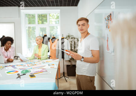 Croquis en main. Closeup portrait of a handsome designer holding un croquis à la main et regardant en face de lui Banque D'Images