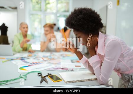 Ouvrez l'ordinateur portable. Jeune femme designer holding un crayon dans sa main tout en regardant dans l'ouverture de cahiers à reliure spirale Banque D'Images
