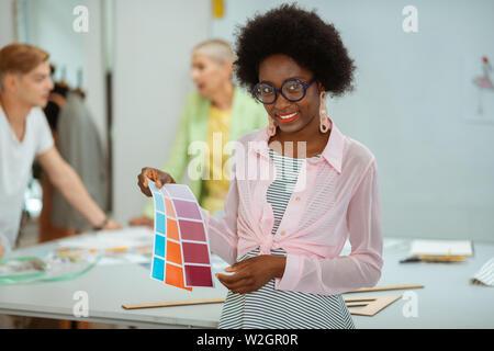 Accessoires élégants. Jolie jeune femme avec des grosses lunettes et boucles d'échantillons couleur tenant dans sa main Banque D'Images