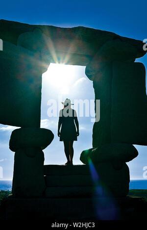 Silhouette d'une femme debout dans une fenêtre encadrée de pierre naturelle à la recherche de l'océan et vers le soleil