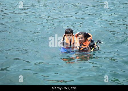 Woman and boy portant un gilet de sauvetage, la plongée dans la mer. Banque D'Images