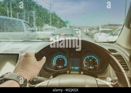 Une part d'un conducteur au volant d'une voiture avec des gouttes de pluie sur le pare-brise en un jour de pluie. La conduite dangereuse car concept. Banque D'Images