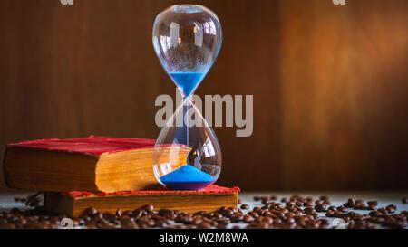 L'horloge de sable sur le vieux livre et de graines de café sur la table en bois. L'espace de copie pour le texte. Le concept de temps à lire des livres. Banque D'Images