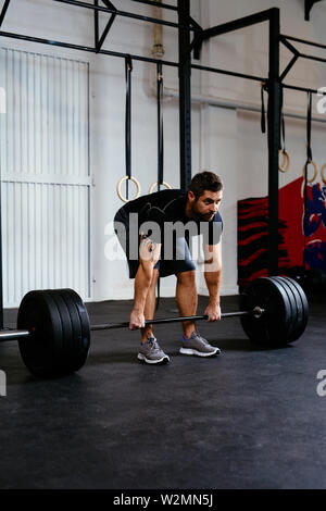Monter man lifting barbell in gym Banque D'Images