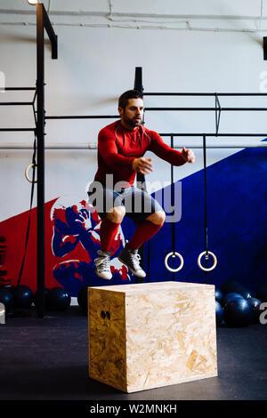 Athletic man jumping sur jump fort au cours de séance de gym Banque D'Images