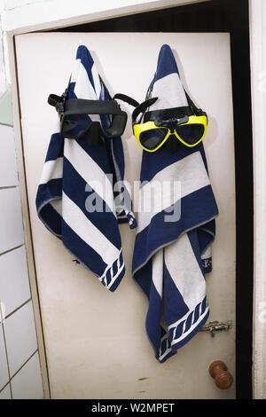 Deux serviettes éponge à rayures avec masques de plongée accrocher sur porte de bois dans le vieux vestiaire Banque D'Images