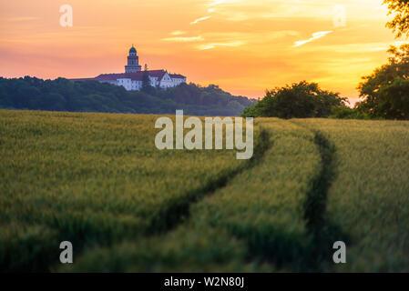 Pannonhalma Archabbey avec champ de blé et le chemin sur l'heure du coucher du soleil en été