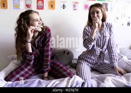 Deux jeunes femmes en pyjama se brosser les dents alors qu'il était assis sur le lit dans la chambre