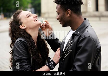 L'application de l'homme brillant à lèvres à la femme, dans la rue en ville, à Munich, Allemagne Banque D'Images