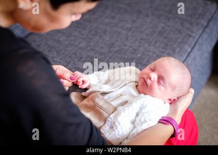 Un tout petit bébé, boy lying on a womans' genoux tenant son doigt. Le bébé est endormi paisiblement, enveloppée dans un cardigan Banque D'Images