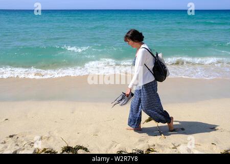 Une femme marchant le long de la rive sur une belle plage à St Ives en Cornouailles Banque D'Images