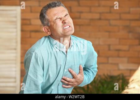Homme mûr souffrant de crise cardiaque à la maison Banque D'Images
