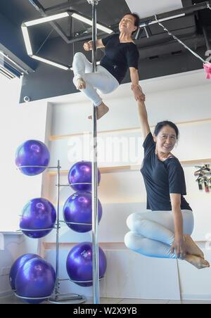 """(190711) -- JILIN, le 11 juillet 2019 (Xinhua) -- Jiang Zhijun (haut) et Li Fengmei pratique pole dancing dans la salle de danse dans la région de Jilin, au nord-est de la Chine La province de Jilin, le 10 juillet 2019. Un groupe de dama, se référant à des légions de femmes d'âge moyen en général, ont formé une équipe de pole dancing in Dunhua City, Jilin Province du nord-est de la Chine en 2016. L'équipe compte huit membres avec une moyenne d'âge de 64 ans. 'Pole Dancing est connu pour sa douceur et sa force,'says Jiang Zhijun, le 68 ans, chef d'équipe."""" Nous avons commencé avec la formation de base de la résistance, puis est allé de l'avant pour effectuer des mouvements de haut niveau progressivement."""" e"""