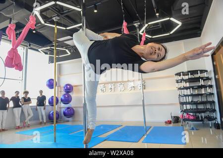 """(190711) -- JILIN, le 11 juillet 2019 (Xinhua) -- Jiang pratiques Zhijun pole dancing dans la salle de danse dans la région de Jilin, au nord-est de la Chine La province de Jilin, le 10 juillet 2019. Un groupe de dama, se référant à des légions de femmes d'âge moyen en général, ont formé une équipe de pole dancing in Dunhua City, Jilin Province du nord-est de la Chine en 2016. L'équipe compte huit membres avec une moyenne d'âge de 64 ans. 'Pole Dancing est connu pour sa douceur et sa force,'says Jiang Zhijun, le 68 ans, chef d'équipe."""" Nous avons commencé avec la formation de base de la résistance, puis est allé de l'avant pour effectuer des mouvements de haut niveau progressivement."""" L'équipe a participé à m"""